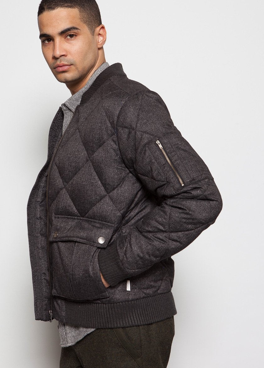 MALE MODEL IN QUILTED BOMBER COAT IN CHARCOAL.  SIDE VIEW WITH HAND IN POCKET