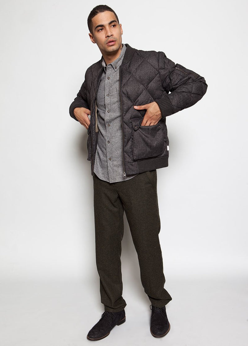 MAN IN QUILTED CHARCOAL BOMBER COAT PLACING HANDS INTO POCKETS, FULL BODY IMAGE.