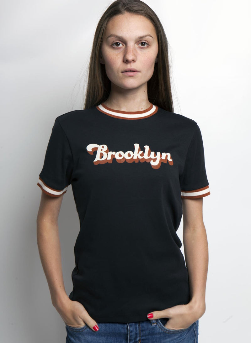 women with hands in pockets wears black radical rib tshirt with orange and white detail