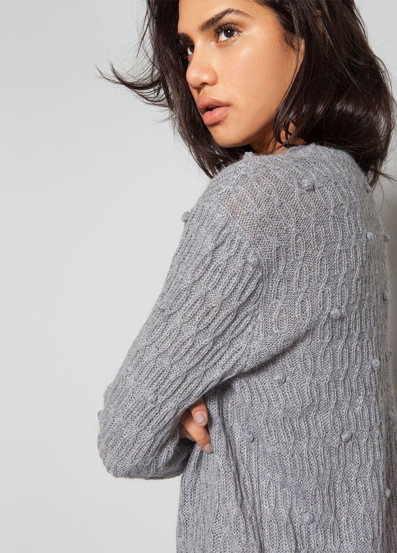 SIDE VIEW OF WOMEN IN GLACIER PEARL SWEATER WITH BOBBLES ARMS CROSSED