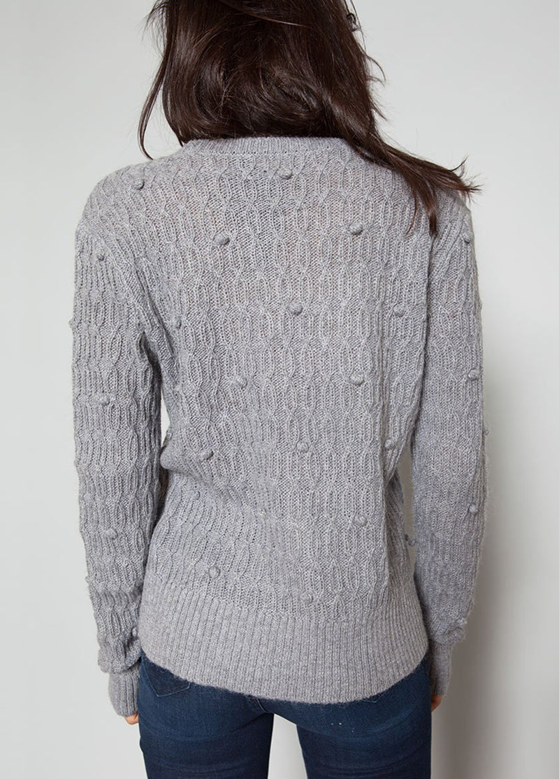 BACK VIEW OF A WOMEN IN A GREY SWEATER WITH BOBBLE DETAILS.