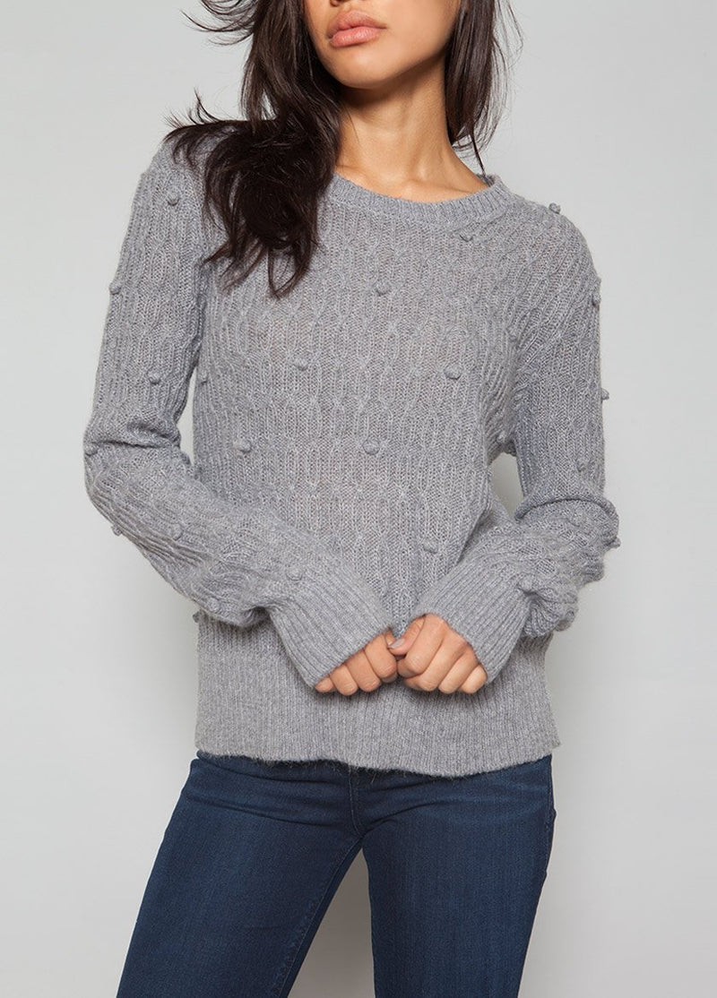 FRONT VIEW OF A WOMEN IN A PEARL SWEATER WITH BOBBLES IN A GREY