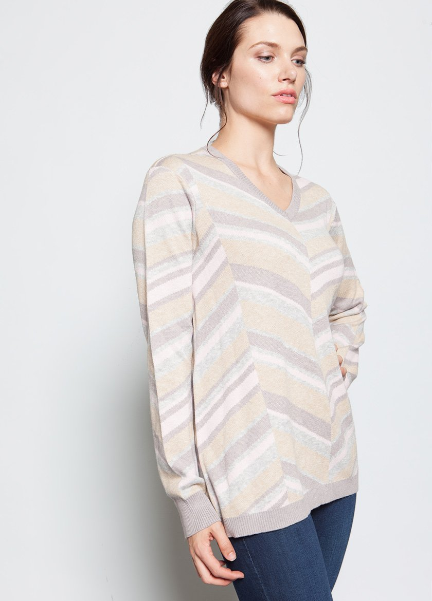 CREME STRIPED SWEATER IN A V STYLE TO THE FRONT CENTER  MODEL STANDING AT ANGLE WITH HAND ON HIP
