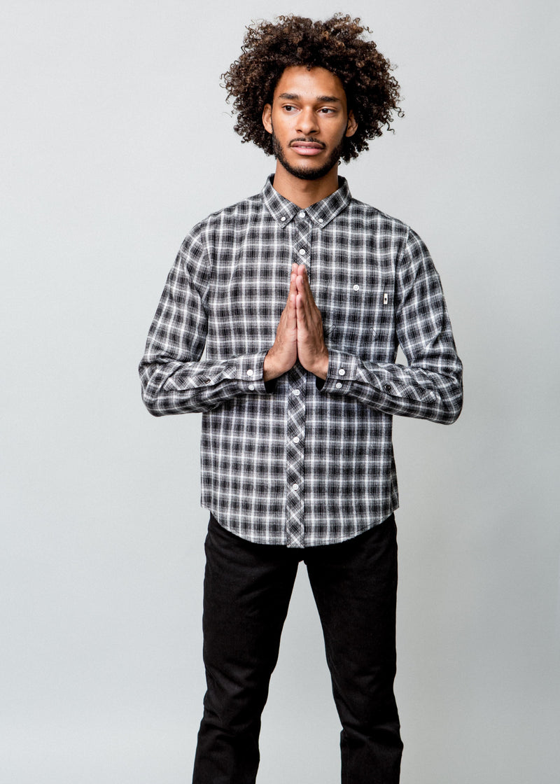 Image of a man wearing a button up black and white check shirt. Hands in prayer position