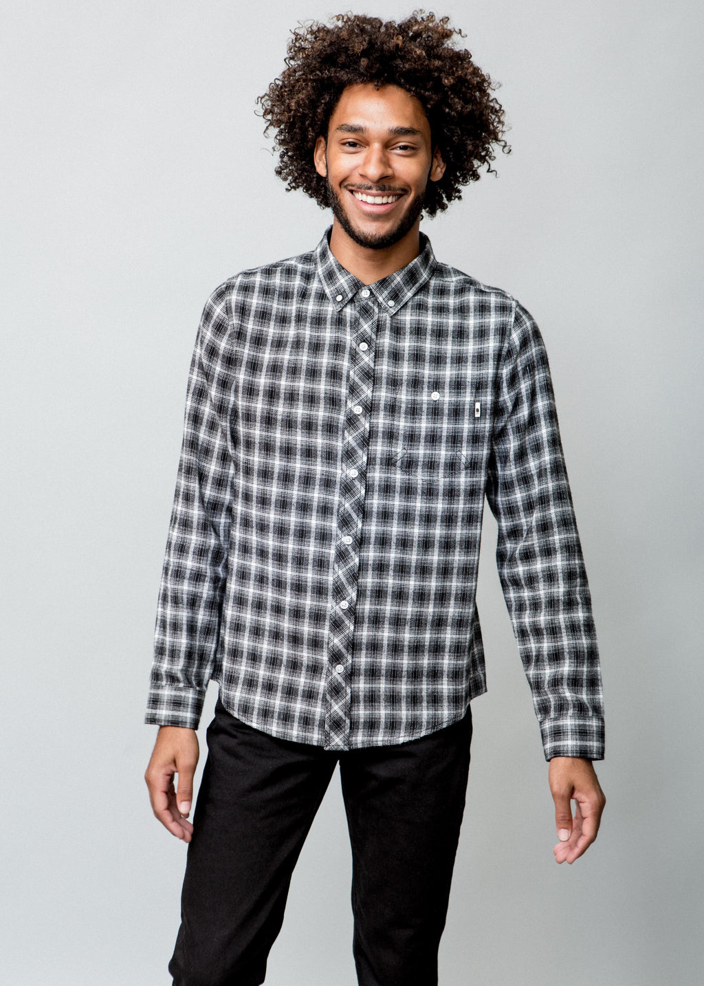 Image of a man wearing a button up black and white check shirt. Front view.