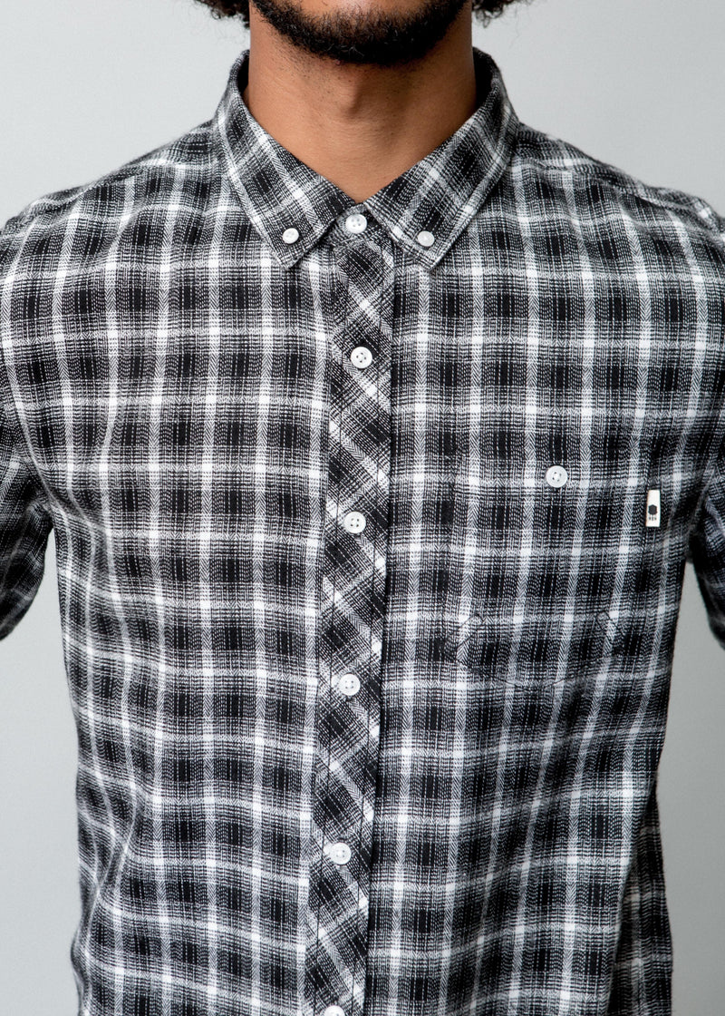 Image of a man wearing a button up black and white check shirt. Close up detail of front of shirt.