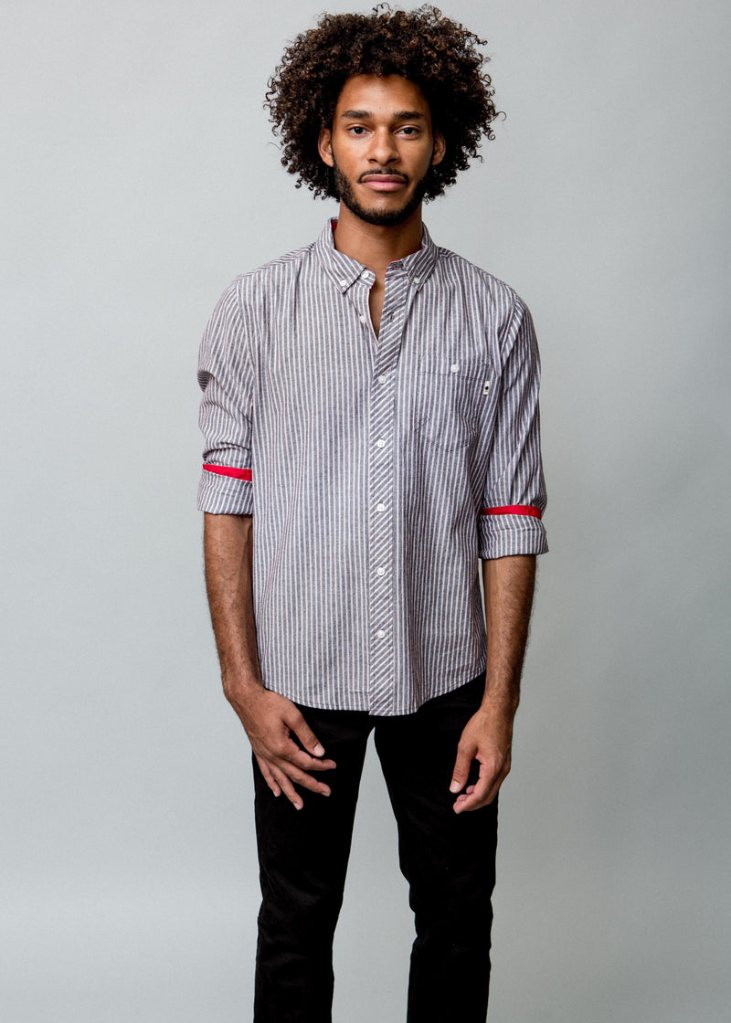 MAN WEARING STRIPED WOVEN DRESS SHIRT WITH STRIPES FRONT VIEW WITH SLEEVES ROLLED TO REVEAL COLOR RED DETAIL