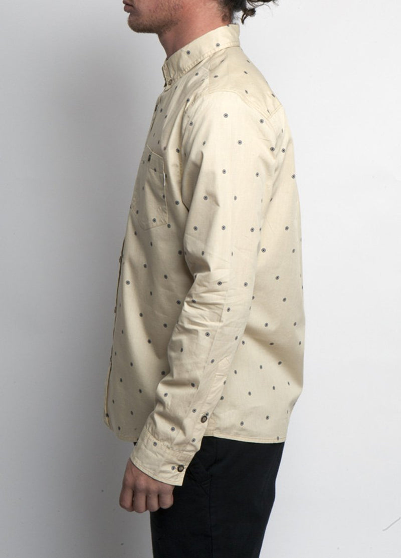 Man is dress shirt, Bolder cream color, with dot design. Side view.