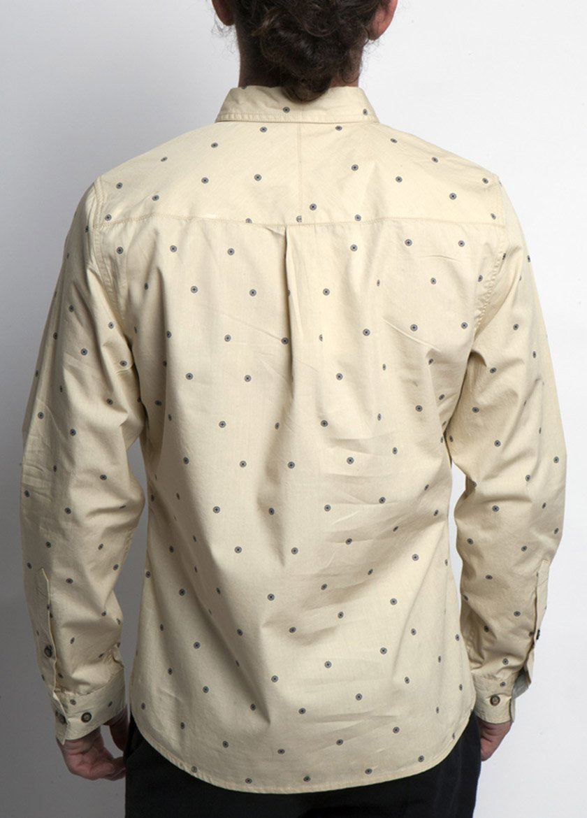 Man is dress shirt, Bolder cream color, with dot design. Back view.