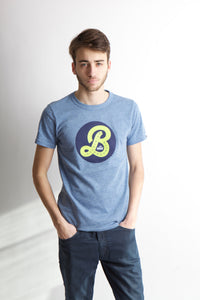 Man looking at camera in mid blue t-shirt with navy blue circle and a large script B letter in yellow.