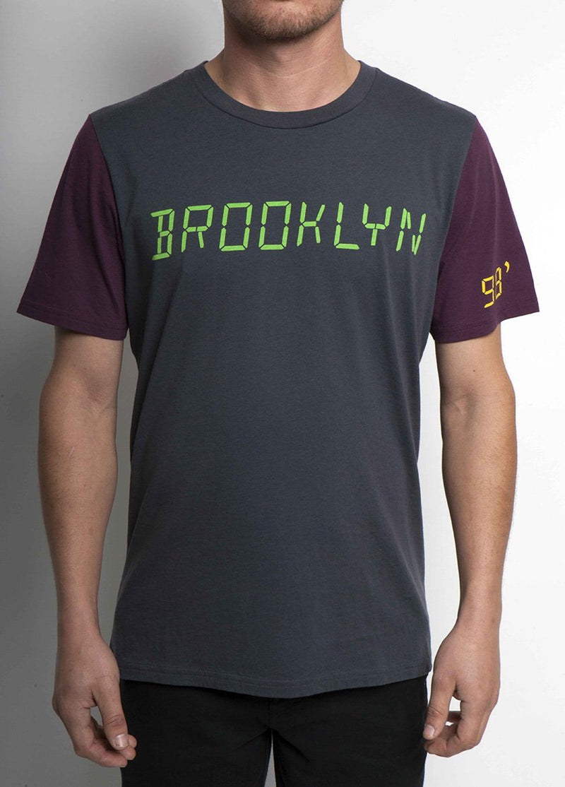 MAN WEARING COAL COLORED TSHIRT WITH BROOKLYN WRITTEN IN A DIGITAL LIME GREEN