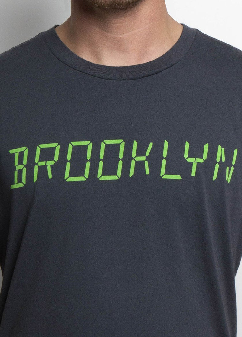MAN WEARING COAL COLORED TSHIRT WITH BROOKLYN WRITTEN IN A DIGITAL LIME GREEN CLOSE UP
