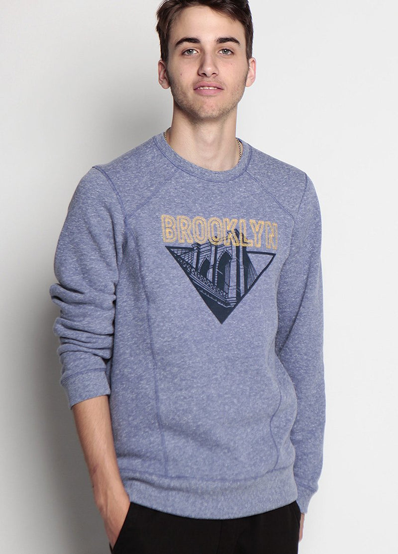 FRONT VIEW OF THE BK BRIDGE STITCHED SWEATSHIRT  IN LIGHT BLUE. IMAGE OF BROOKLYN BRIDGE IN CONTASTING COLOR, BROOKYLN WRITTEN IN YELLOW, STITICHING DETAIL DOWN THE BODY OF THE SWEATER