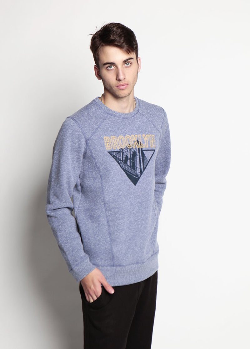 MAN WIHT ONE HAND IN HIS POCKET, LOOKS AT THE CAMERA WEARING THE BK BRIDGE STITCH SWEATSHIRT IN BLUE