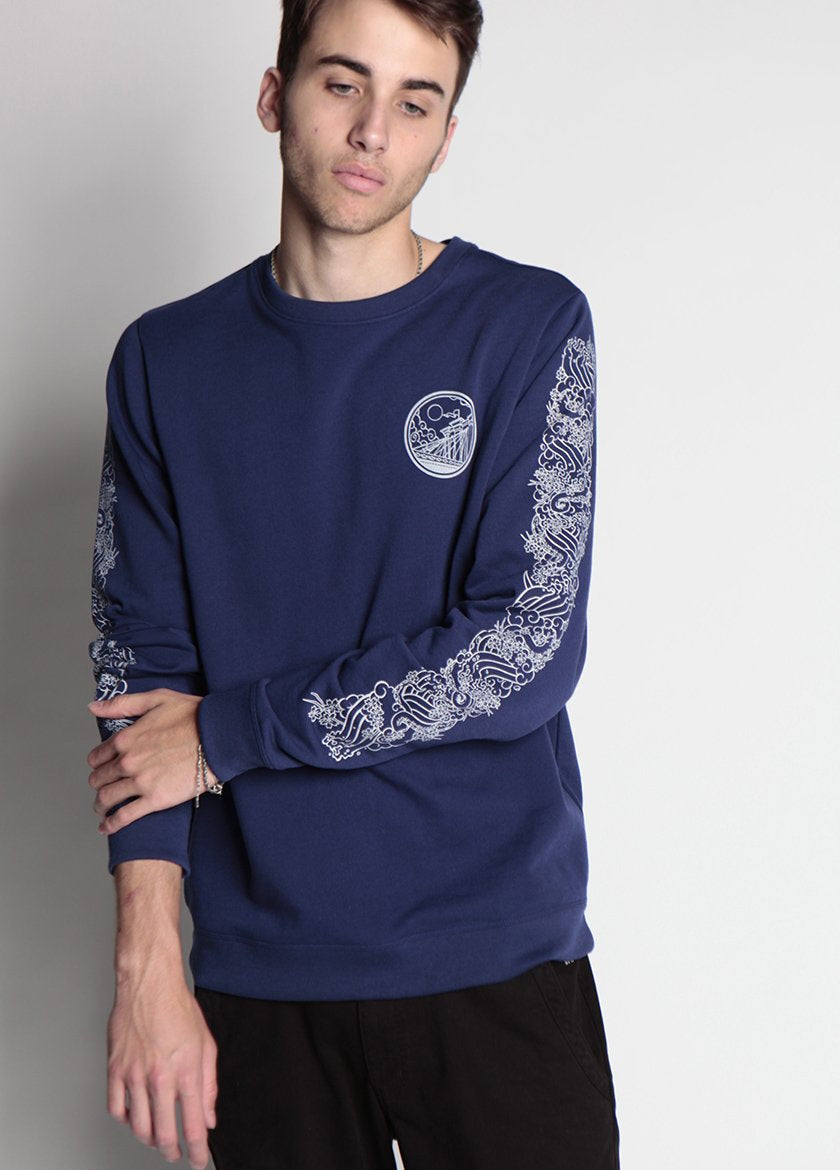 mAN PULLS ON SLEEVE IN BLUE BROOKLYN INDUSTRIES SWEATSHIRT
