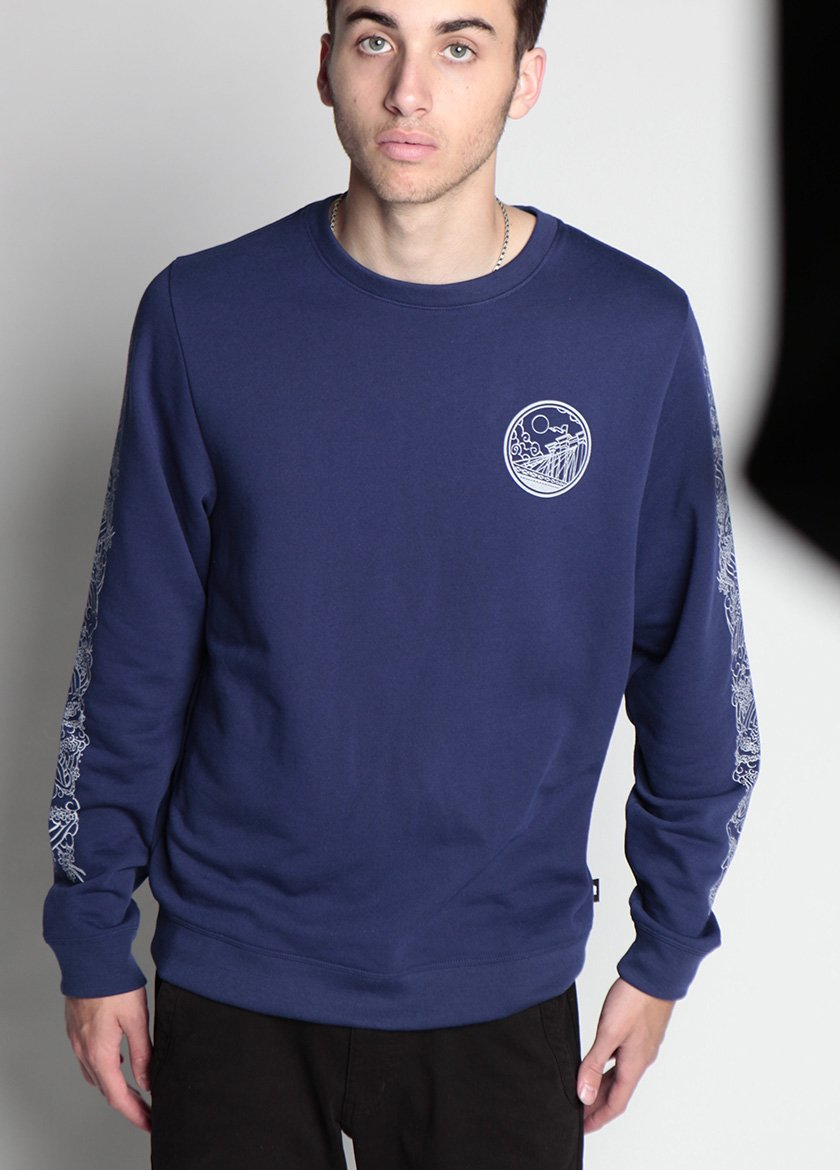 MAN LOOKS AT CAMERA IN BLUE BRIDGE MONSTER SWEATSHIRT