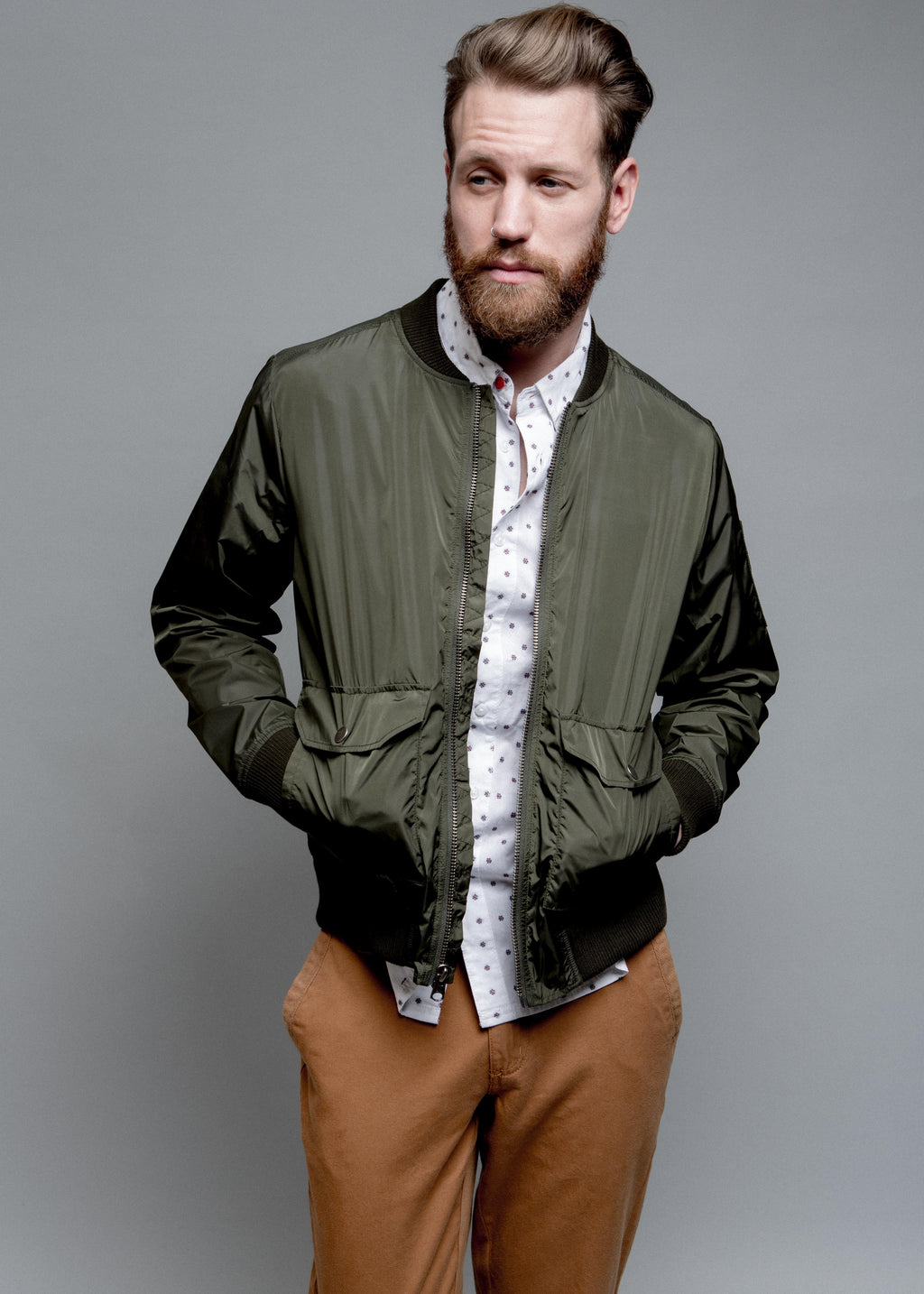 NYLON BOMBER JACKET IN GREEN ON MALE MODEL. OPEN FRONT HANDS IN POCKETS