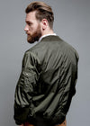 DETAIL OF BACK NYLON BOMBER JACKET IN GREEN ON MALE MODEL