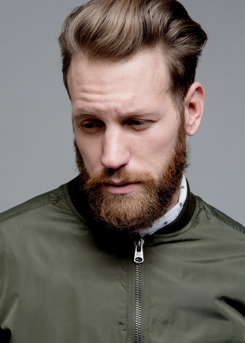 NYLON BOMBER JACKET IN GREEN ON MALE MODEL, CLOSE UP OF THE TOP OF JACKET