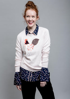 Woman smiling and wearing a light pink sweater with a rooster on the front.
