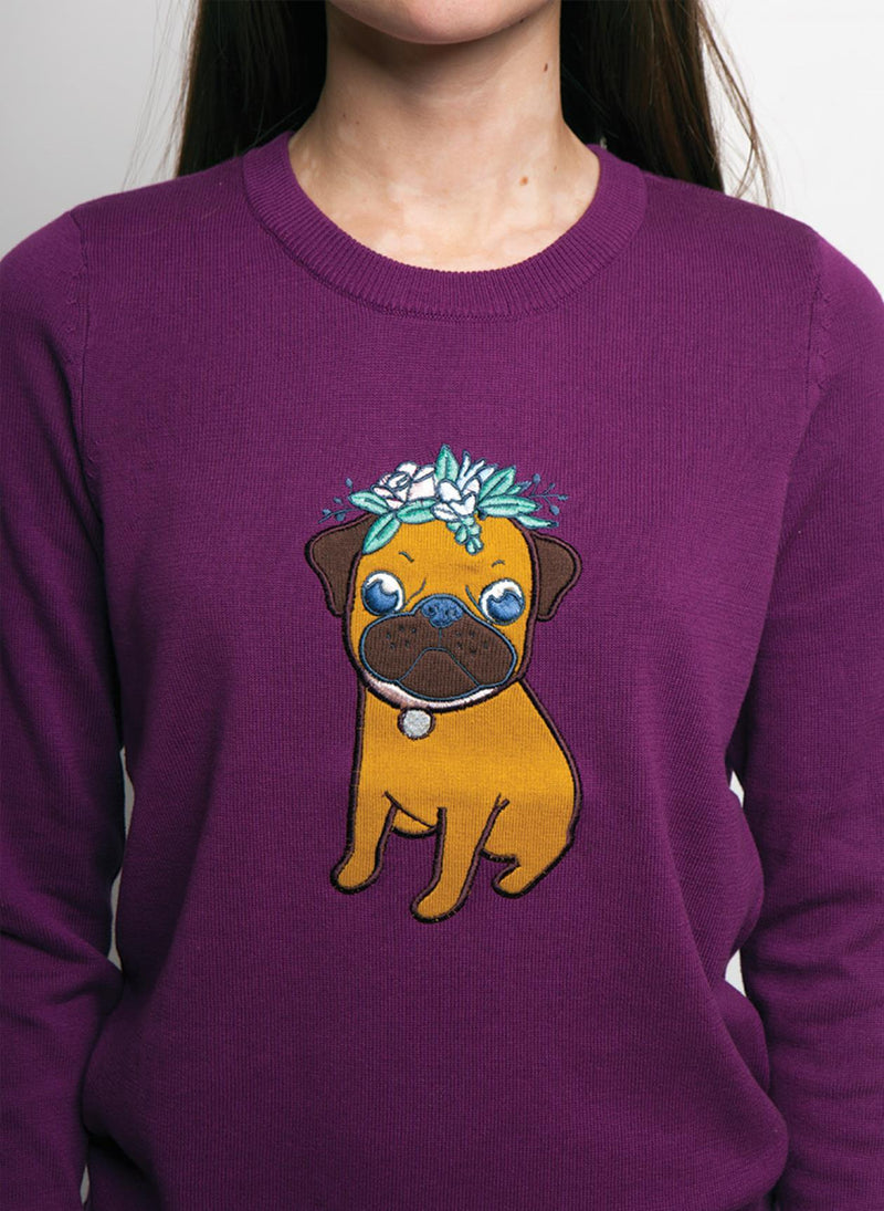 DETAIL OF PURPLE SWEATER WITH A COLORFUL PUG DOG, ON WOMEN MODEL ARMS TO SIDES