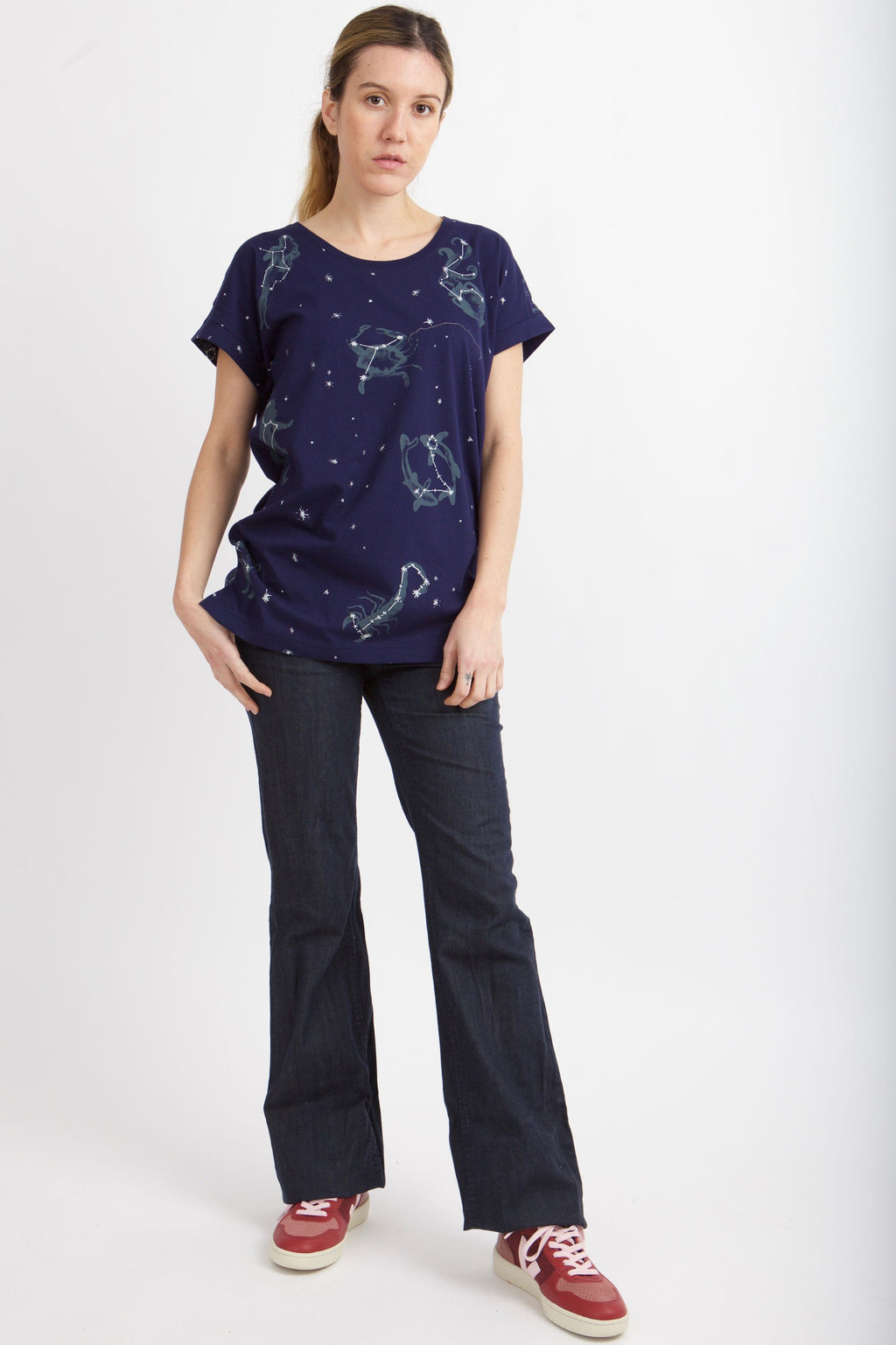 women wears blue shirt with cuffed sleeves, zodiac symbols and star details all  over the shirt pants and red shoes