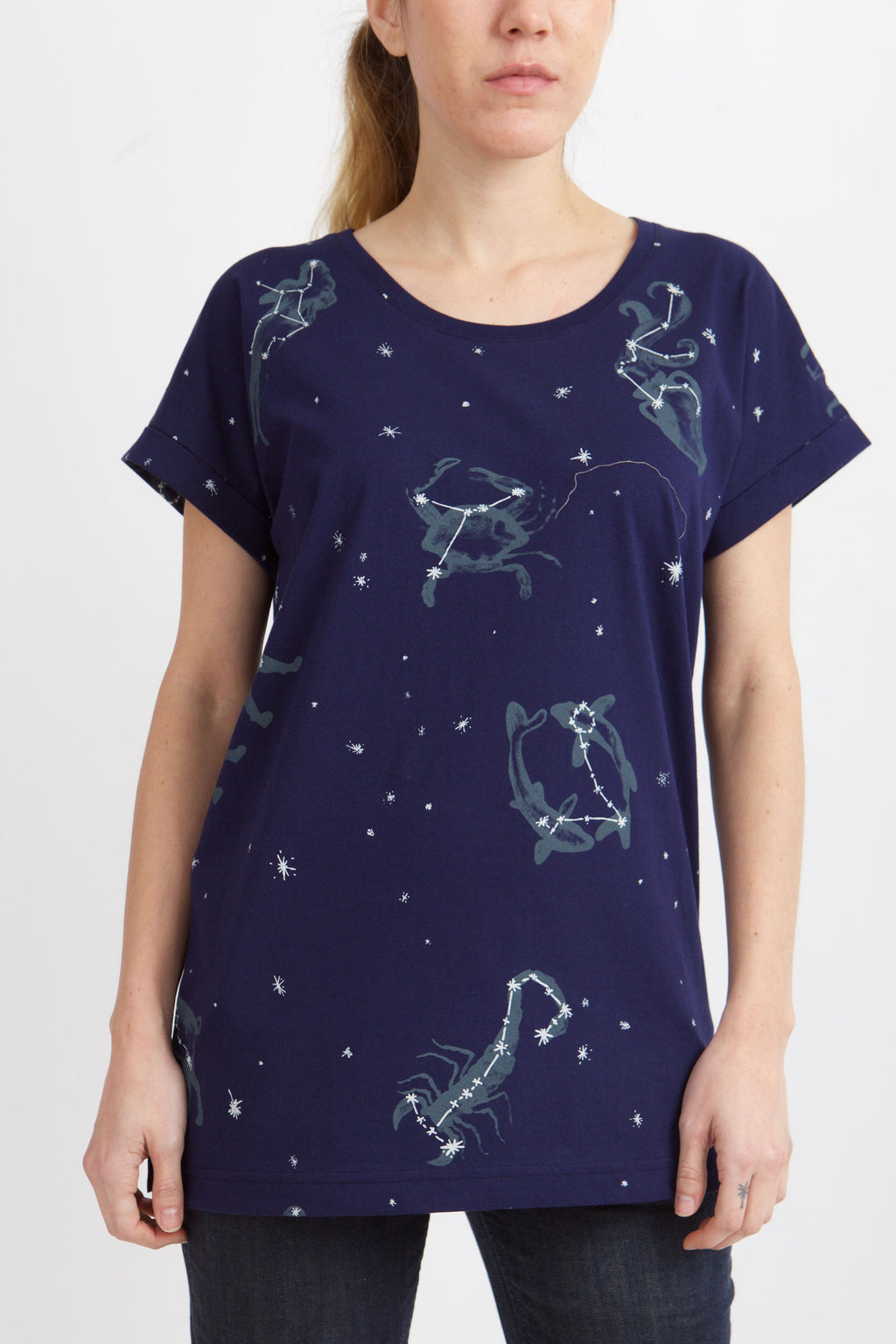 women wears blue shirt with cuffed sleeves, zodiac symbols and star details all  over the shirt