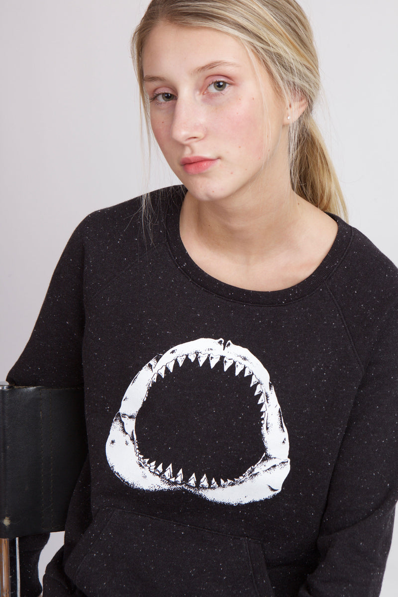 Close up of woman wearing black sweatshirt with white shark mouth.
