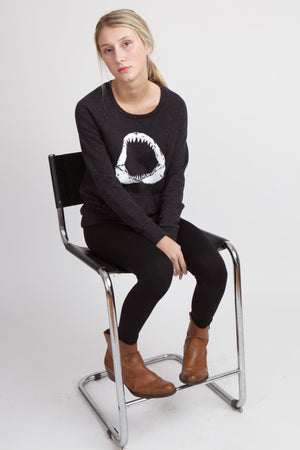 Woman in black sweatshirt with white shark mouth printed on her front seated on a black chair.