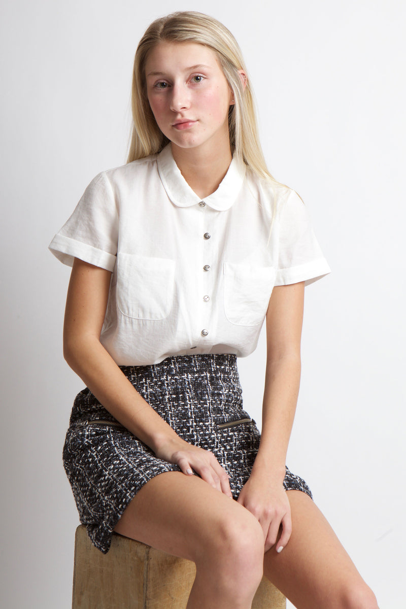 Woman seated on box of wooden box in tweed skirt and white button up short sleeve top