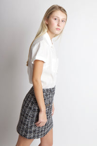 woman leaning over in white shirt and tweed skirt.