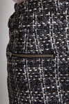 Close up of tweed fabric in black, grey and white stitching with zipper.