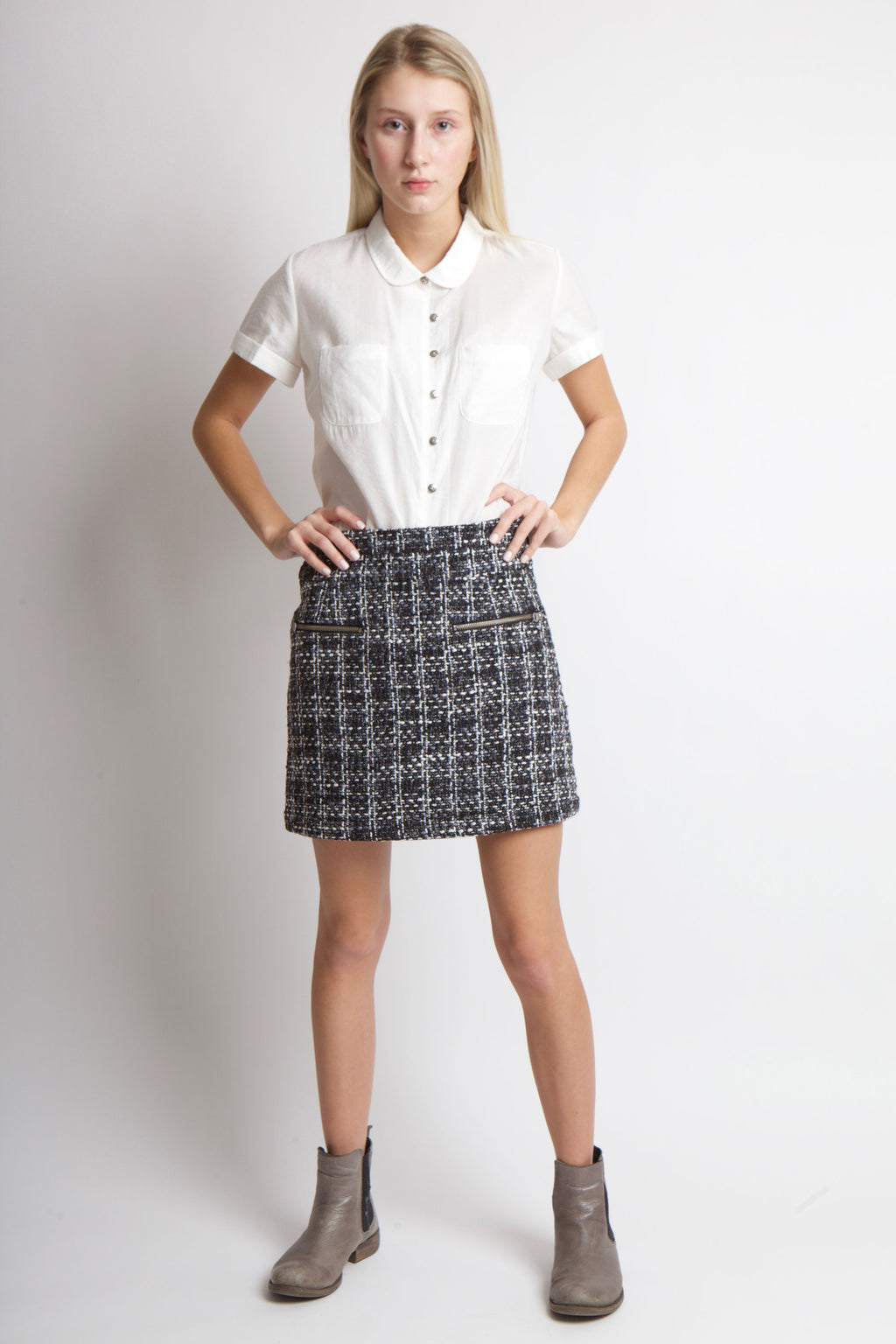 Woman standing with tweed mini skirt, white shirt and grey shoes.