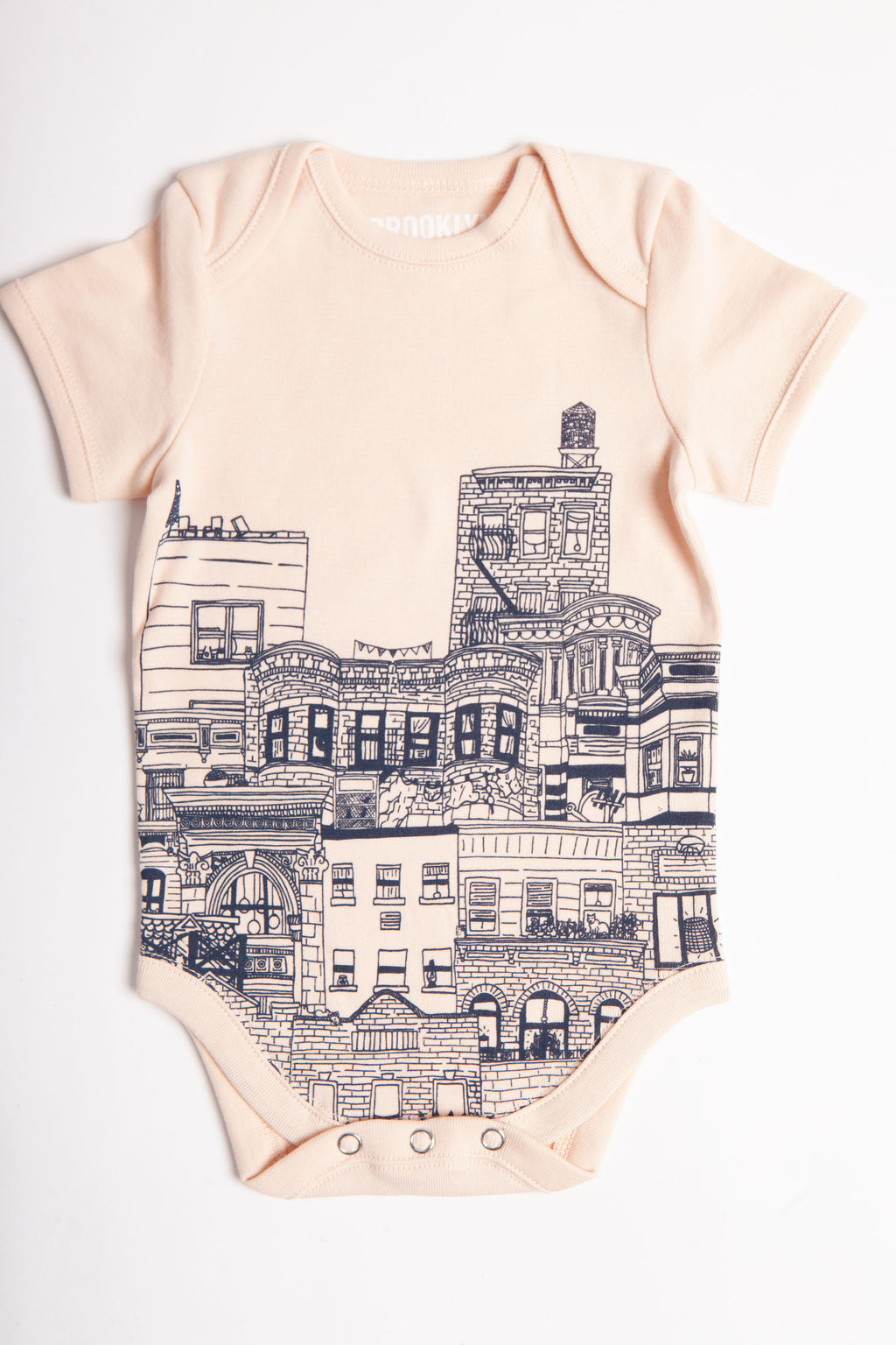Linen colored infant onesie with hand-drawn buildings showing windows, rooftops and a watertower.