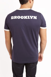 Back view of men's Comma t-shirt with Brooklyn written in white lettering across shoulder bladed.  The O's of Brooklyn are comma's.