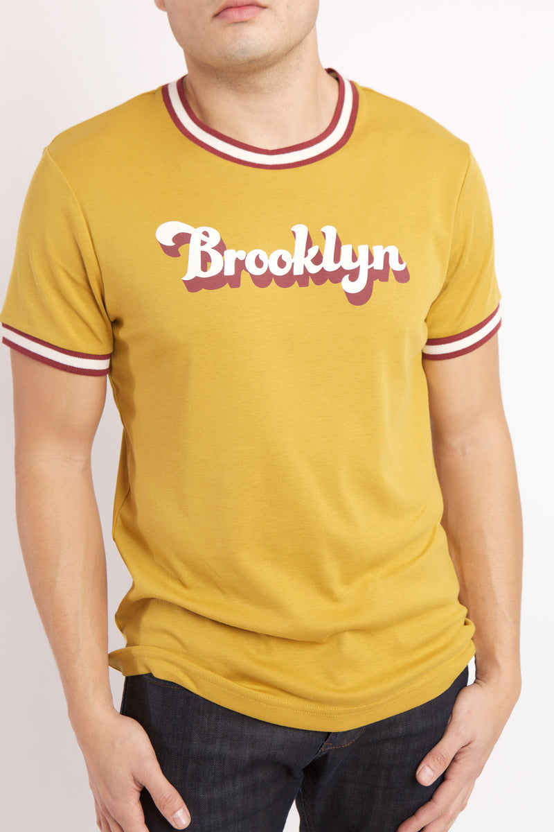 DETAIL OF THE WHITE AND RED BROOKLYN TEXT ON YELLOW RADICAL RIBBED KNIT SHIRT WITH WHITE AND RED BANDING DETAIL ON SLEEVE AND COLLAR