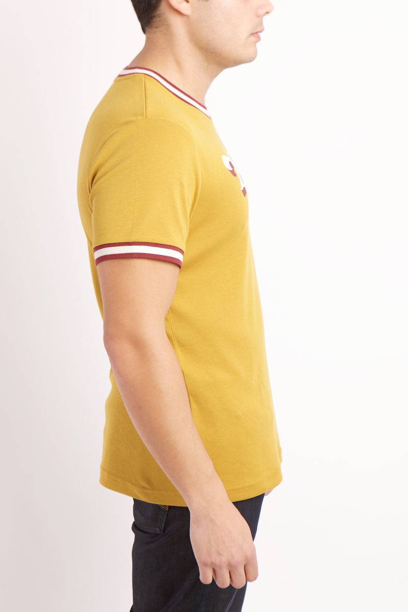 SIDE VIEW OF THE WHITE AND RED BROOKLYN TEXT ON YELLOW RADICAL RIBBED KNIT SHIRT WITH WHITE AND RED BANDING DETAIL ON SLEEVE AND COLLAR