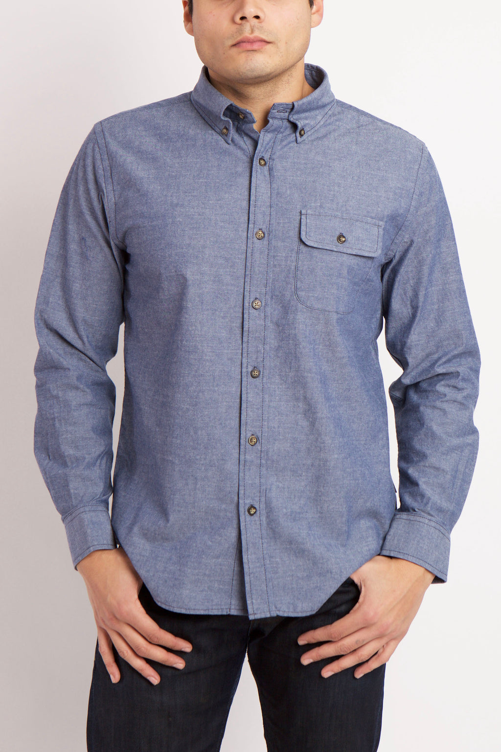 MAN WEARS BLUE BUTTON UP WOVEN SHIRT WITH HANDS IN POCKETS