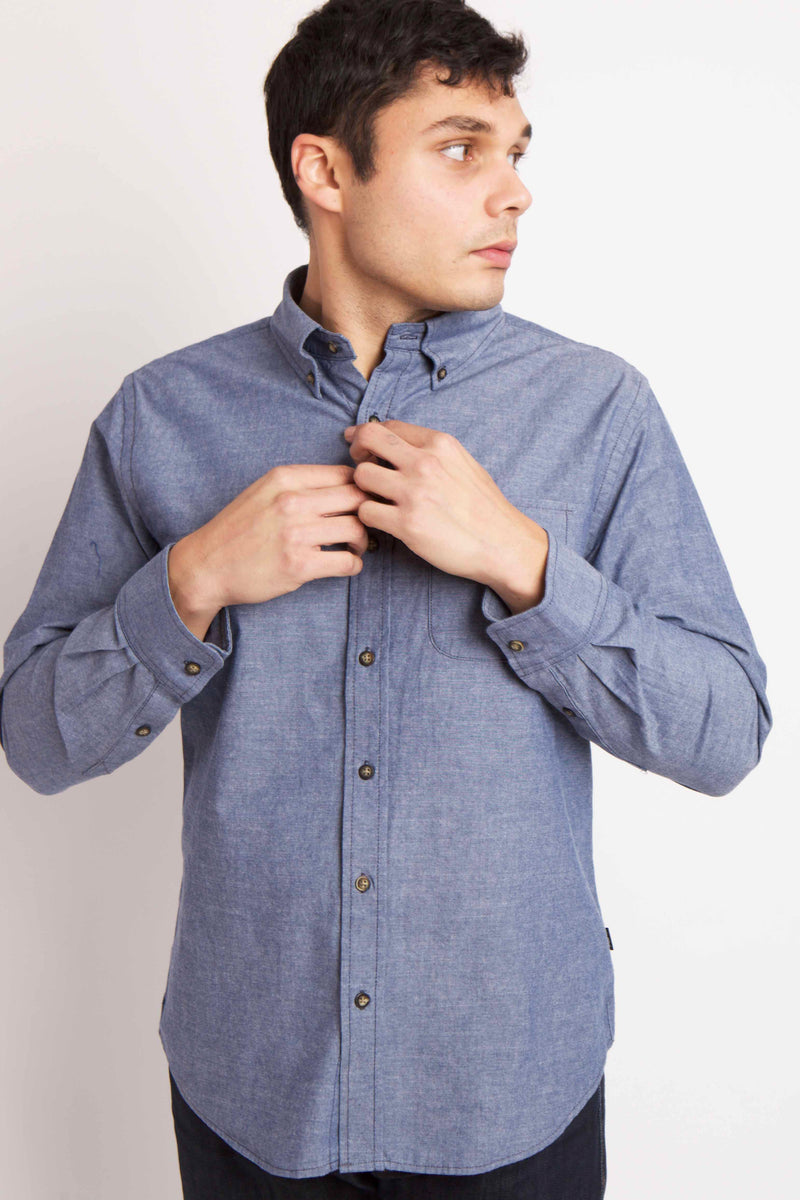 MAN WEARS BLUE BUTTON UP WOVEN SHIRT, LOOKS TO THE LEFT WHILE BUTTONING THE TOP