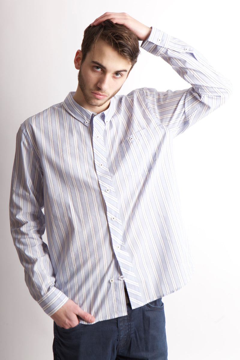 Man wearing vertical stripe blue and white woven shirt with left hand on top of his head looking at camera.