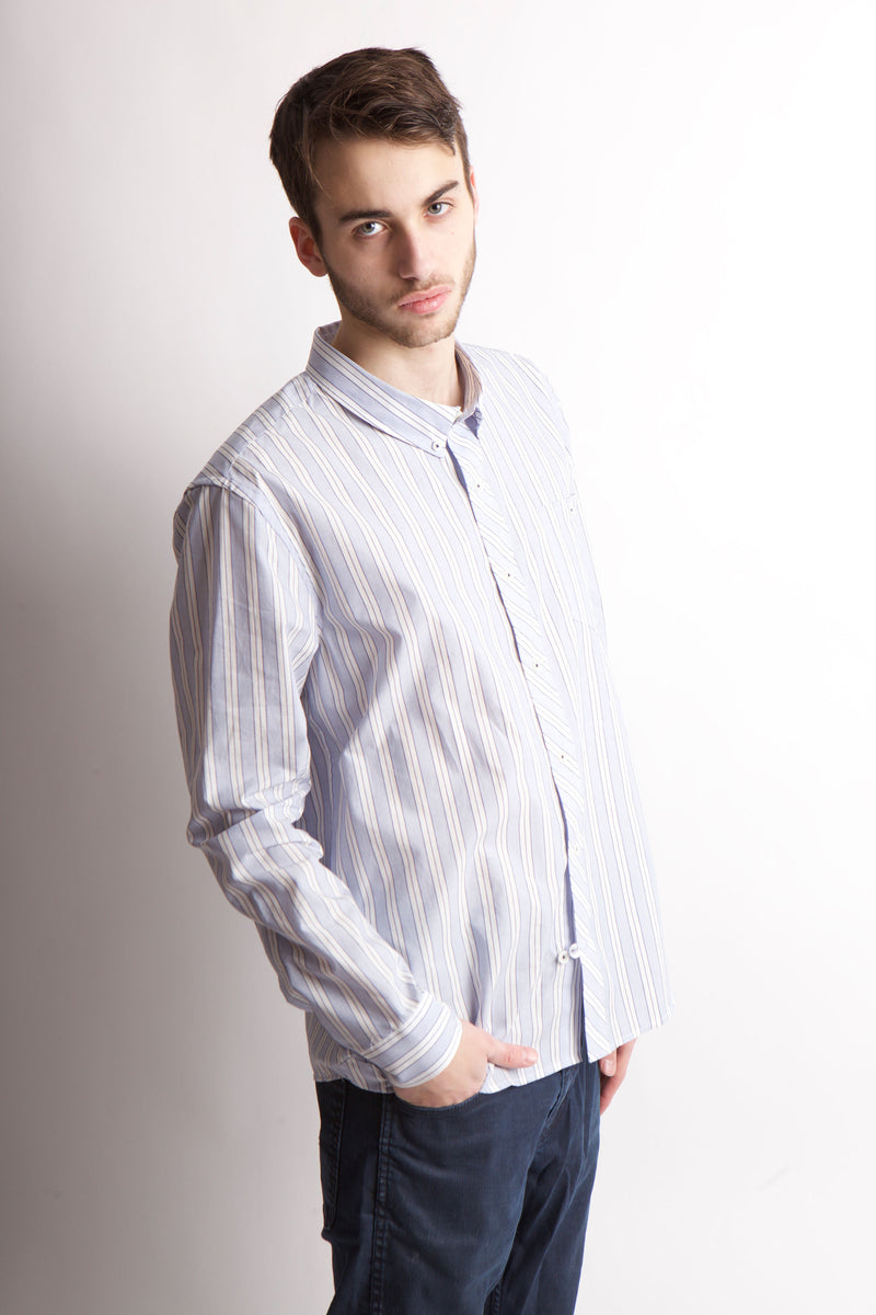 Side view of man looking at camera with right hand in jean pocket.  He is wearing a striped long sleeve button shirt.