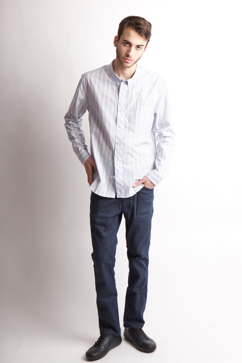 Full frontal image of man wearing a long sleeve blue and white stripe shirt, denim pants and black shoes.
