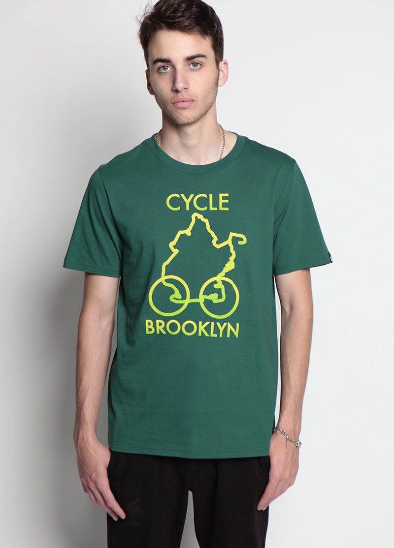 man looks into the camera, wearing black pants and a green shirt that says cycle brooklyn, a yellow and neon pattern depict the borough outline, with wheels