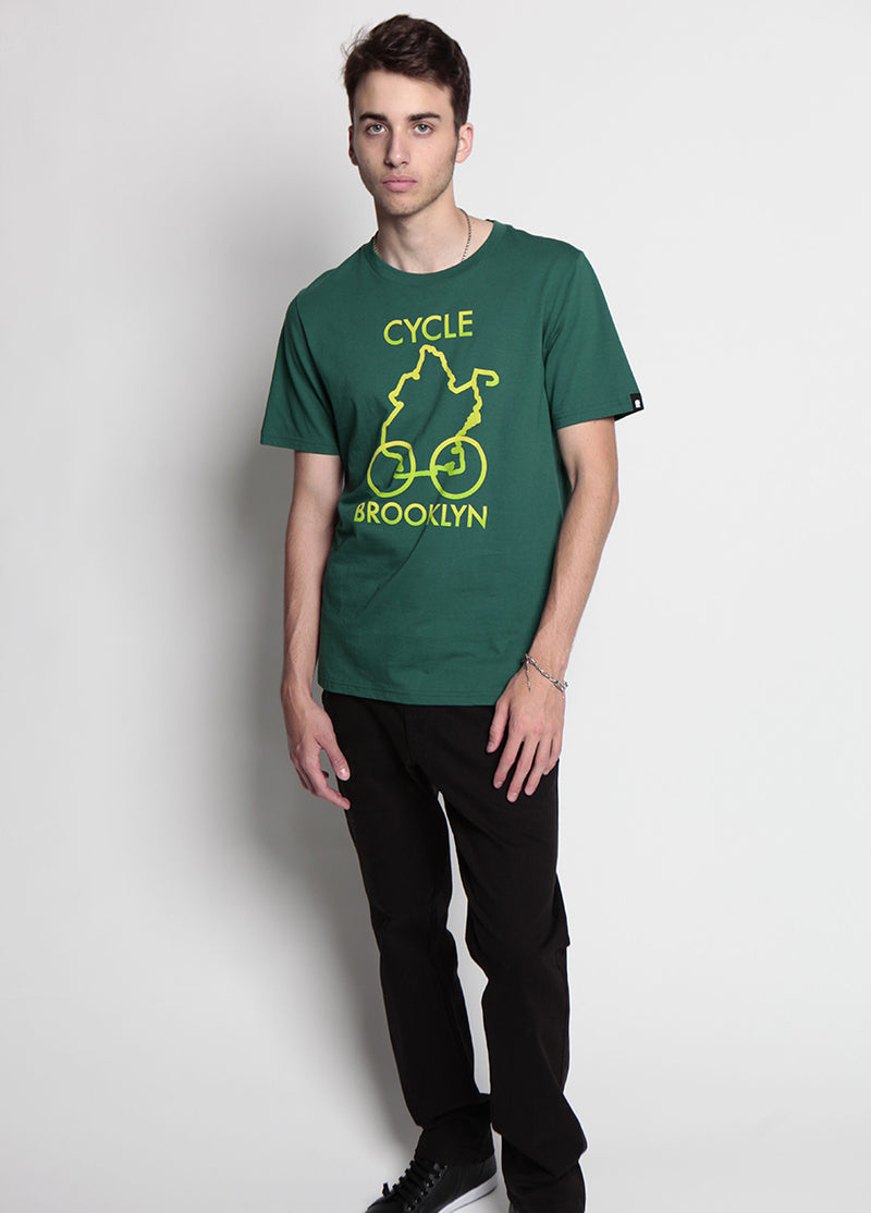 full body in the frame of man looks into the camera, wearing black pants and a green shirt that says cycle brooklyn, a yellow and neon pattern depict the borough outline, with wheels