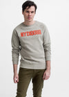 MAN WEARS SMOKE COLORED SLIPPED BK SWEATSHIRT WITH ORANGE TEXT