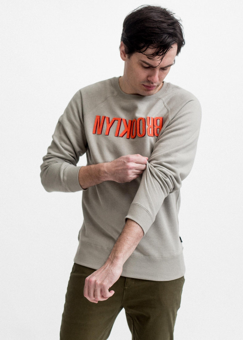 MAN LOOKS DOWN WEARING SMOKE COLORED SLIPPED BK SWEATSHIRT WITH ORANGE TEXT