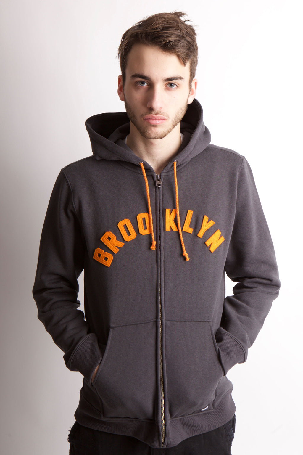 MAN WEARS GREY HOODED SWEATSHIRT WITH HAND IN THE FRONT JOEY POUCH POCKET. BROOKLYN IN APPLIQUE LETTERS ACROSS THE CHEST IN AN ORANGE COLOR.