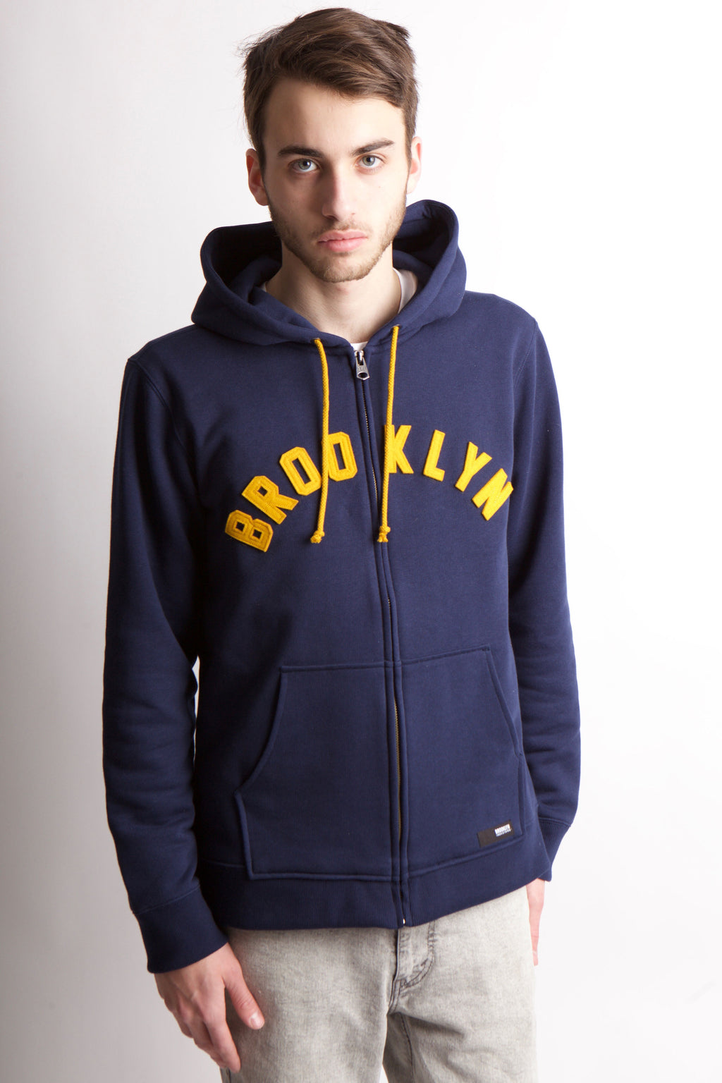 "Navy Sweatshirt with front zip and hood with the words ""Brooklyn"" in felt applique arched across the chest.  Yellow strings hang down from hood."
