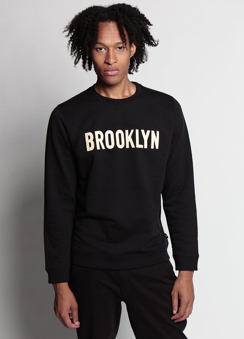 MAN WEARS BLACK FLAT BROOKLYN SWEATSHIRT