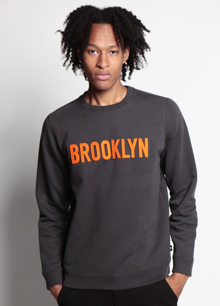 MEN WEARS GREY SWEATSHIRT WITH ORANGE BROOKLYN TEXT FLAT ACROSS THE CHEST